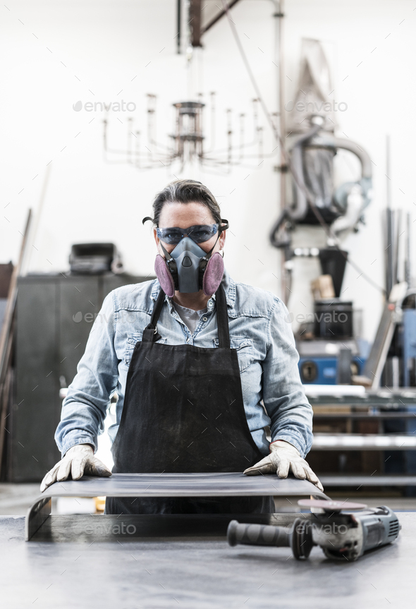Woman wearing safety glasses and dust mask standing in metal workshop, looking at camera. - Stock Photo - Images
