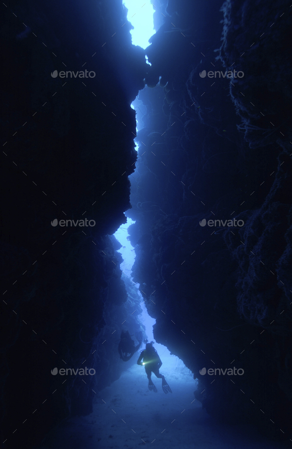 Dramatic silhouette of diver in reef crevice. - Stock Photo - Images