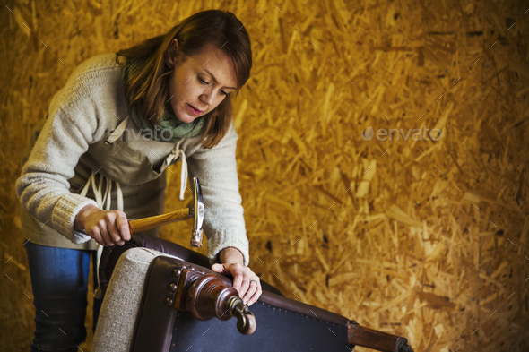 Upholstery workshop. An upholsterer using a hammer to secure fabric and padding to a chair leg. - Stock Photo - Images