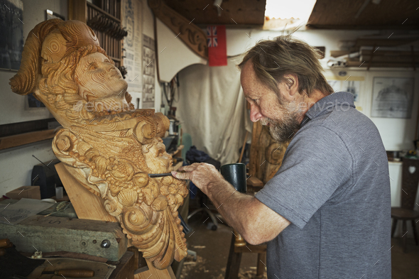 A craftsman, a wood carver working on a wooden female ship's figurehead held in a vice on the - Stock Photo - Images