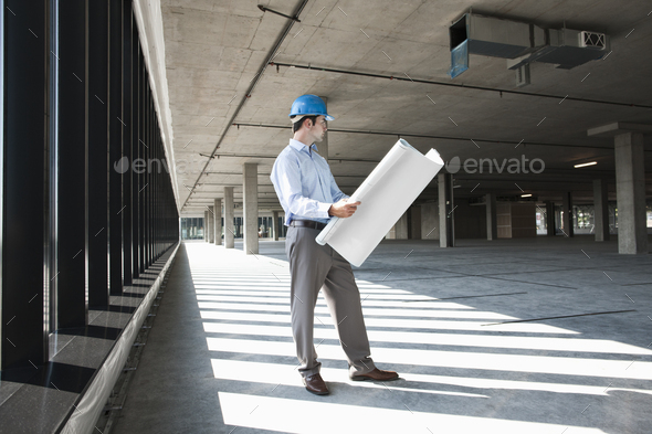 Caucasian businessman holding plans for a new office in a large empty raw office space. - Stock Photo - Images