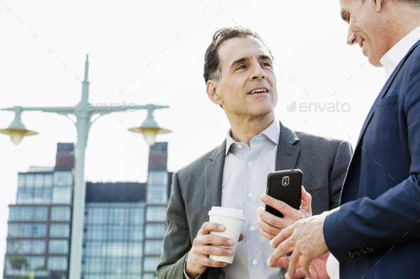 Two people, men talking together outdoors leaning on a railing, taking a coffee break. - Stock Photo - Images
