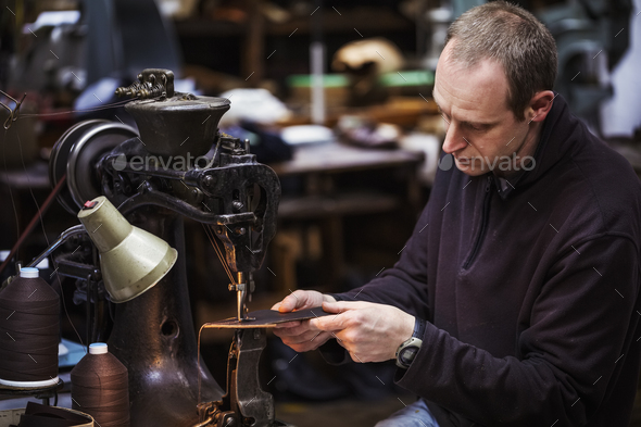 Man sitting at a large leather stitching machine in a shoemaker's workshop. - Stock Photo - Images