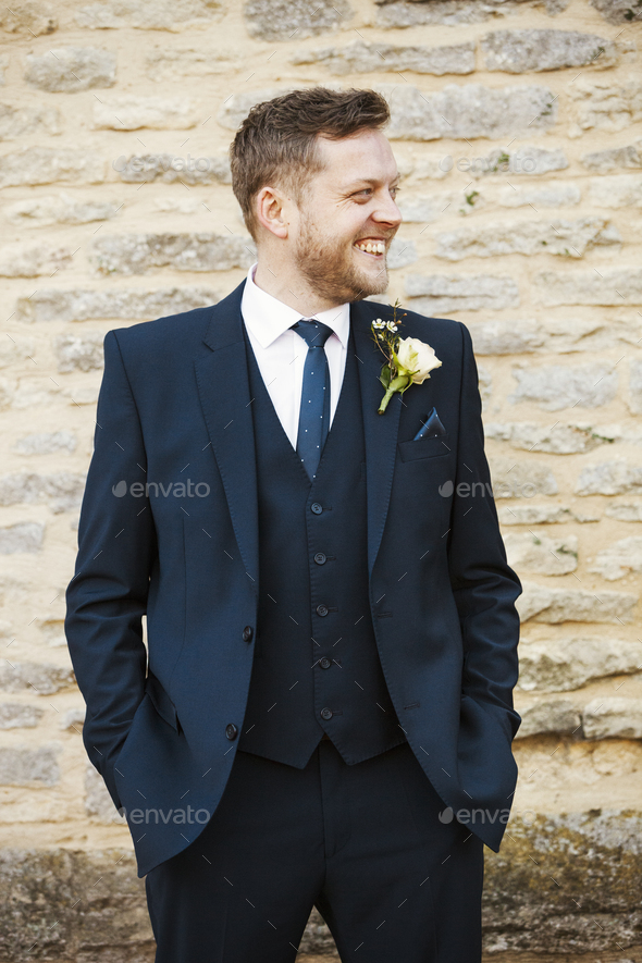 A man in a suit with a buttonhole with his hands in his pockets, smiling. - Stock Photo - Images