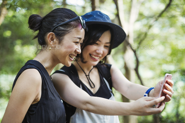 Two young women standing in a forest, taking a selfie. - Stock Photo - Images