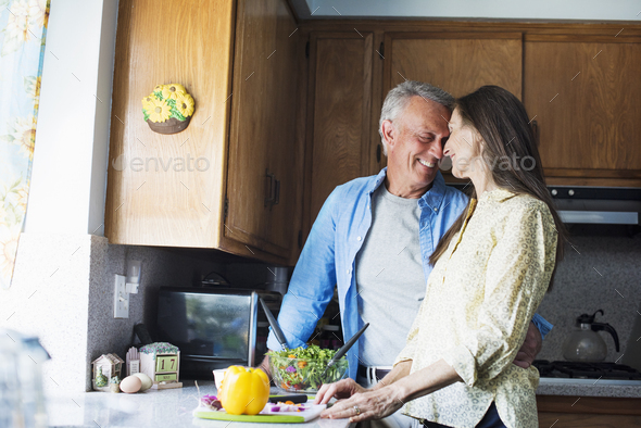 Smiling senior couple standing in a kitchen, preparing food. - Stock Photo - Images