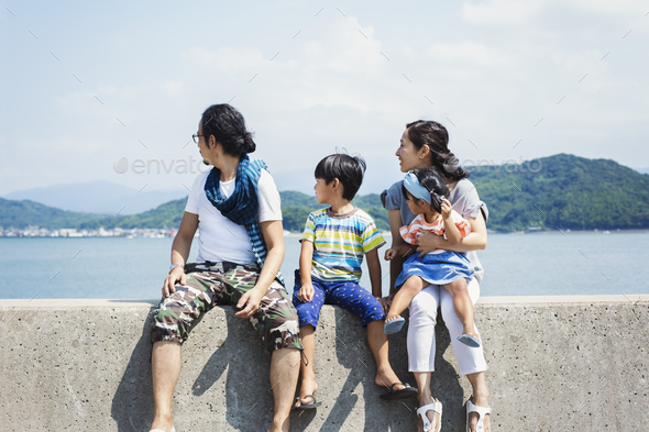 Family, man, boy and woman with young girl on her lap sitting side by side on a wall by the ocean. - Stock Photo - Images