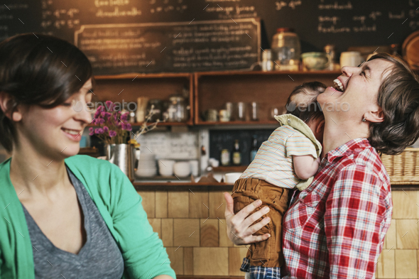 Two women, a same sex couple with their 6 month old baby in their coffee shop. business owners and - Stock Photo - Images