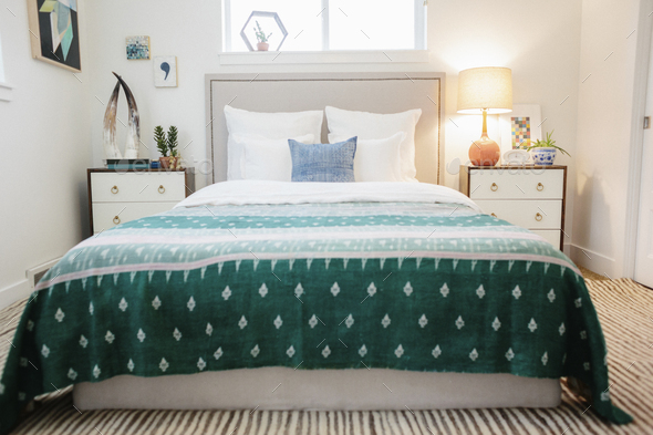 A bedroom in an apartment with a double bed  and a jade green patterned bed cover. - Stock Photo - Images