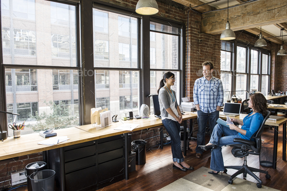 Mixed race group of people meeting to brainstorm an issue in a creative office. - Stock Photo - Images