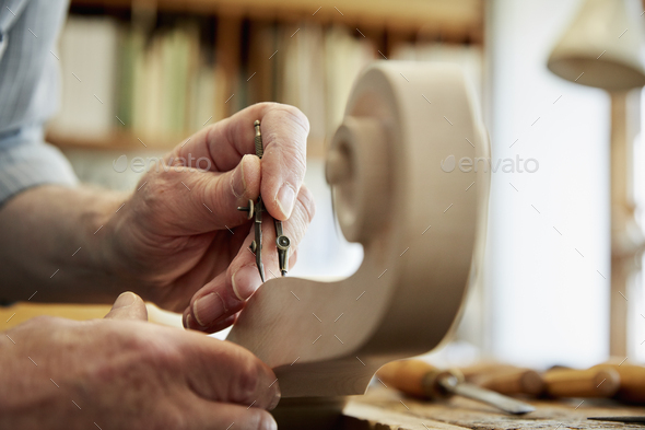 A violin maker working in his workshop, using hand tools to shape and chisel the curled scroll of - Stock Photo - Images