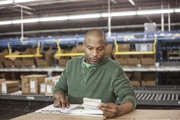 Working portrait of an African American warehouse worker in a large distribution warehouse. - Stock Photo - Images