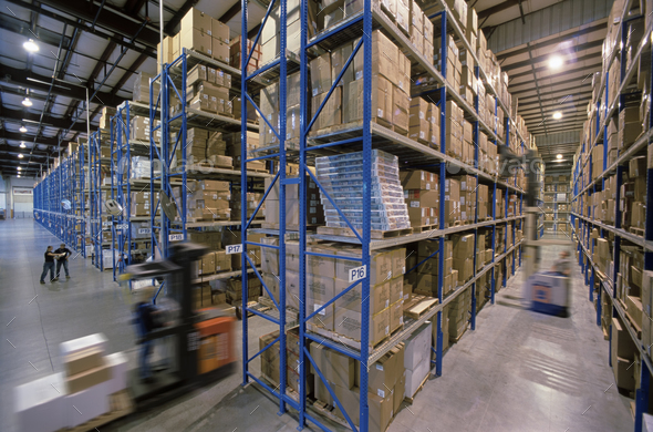 Overview of a large industrial distribution warehouse storing products in cardboard boxes on - Stock Photo - Images