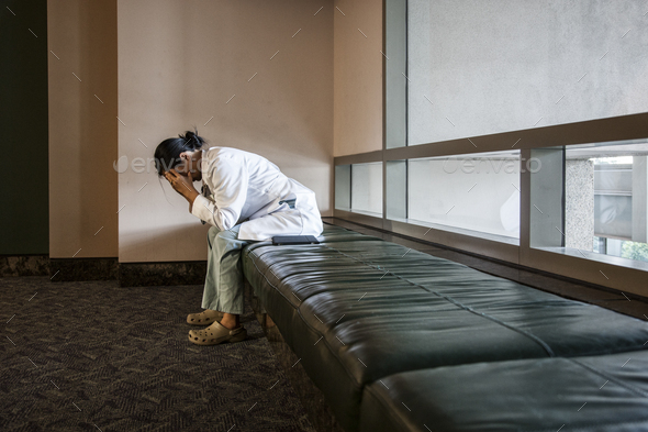 Asian woman doctor under stress sitting on a bench in a hospital. - Stock Photo - Images