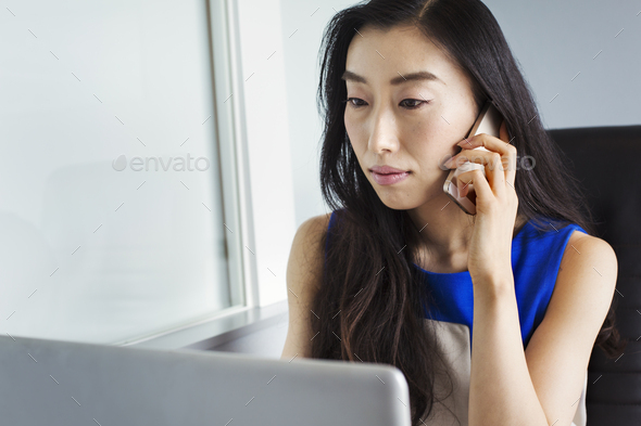 A business woman preparing for work, sitting using her laptop and talking on her smart phone. - Stock Photo - Images