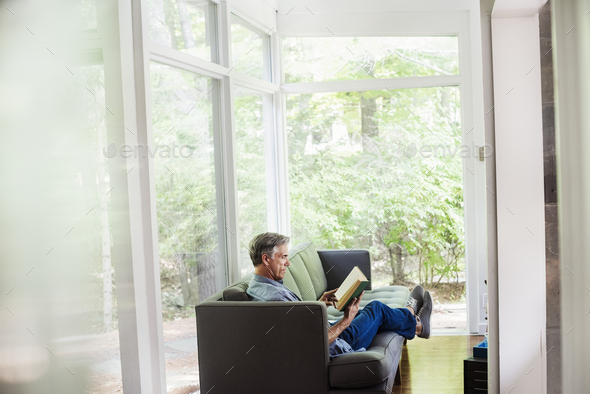 A man sitting by a window on a sofa, reading a book. - Stock Photo - Images