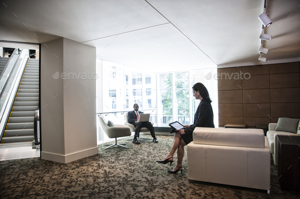 Caucasian businesswoman and black businessman working on computers in the lobby area of a large - Stock Photo - Images