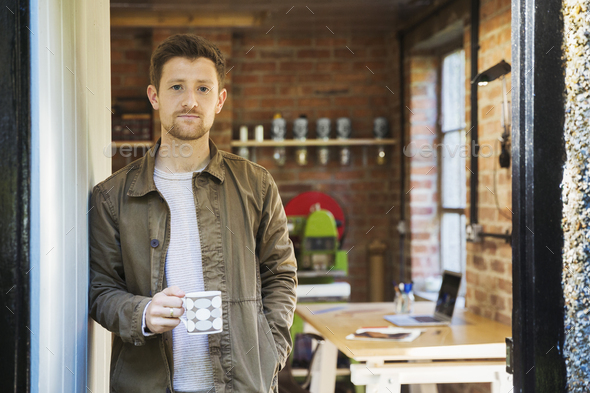 A young man standing at a workshop door, holding a coffee cup. - Stock Photo - Images