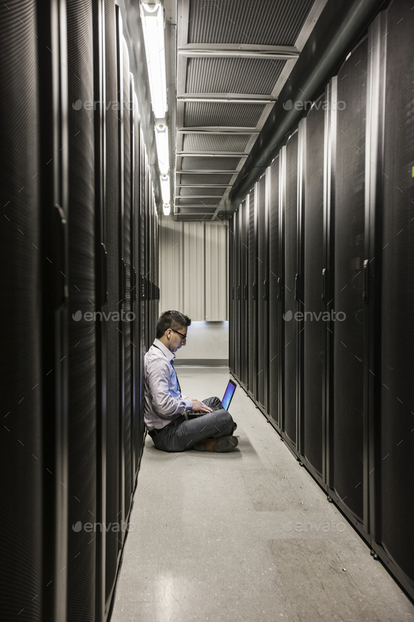 Hispanic man technician doing diagnostic tests on computer servers in a large server farm. - Stock Photo - Images