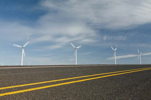 Wind turbines, tall white towers in the flat plains by a road near the Columbia River Gorge. - Stock Photo - Images