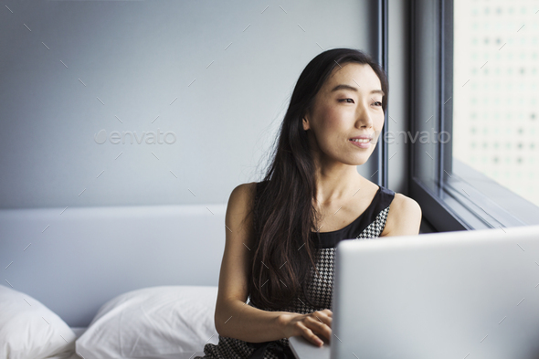 A business woman dressed, sitting on her bed using a laptop. - Stock Photo - Images