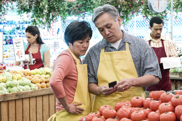 man and woman wearing aprons standing at stall with fresh tomatoes at a fruit and vegetable market. - Stock Photo - Images