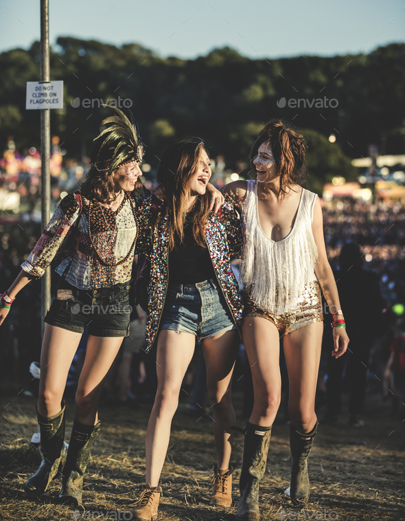 Three young women at a summer music festival wearing hot pants and Wellington boots, feather - Stock Photo - Images