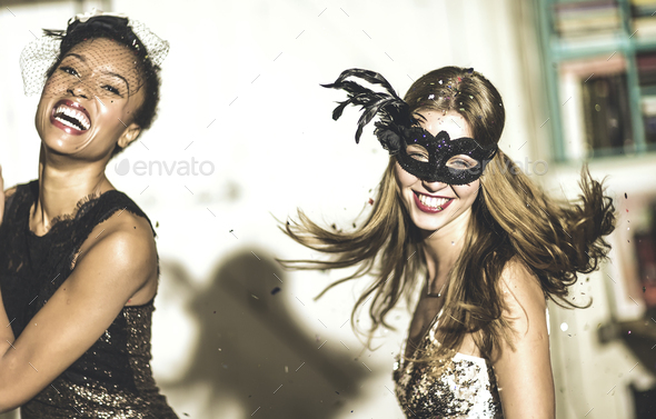 Two young women at a party in sequined dresses drinking and laughing, one wearing a face mask. - Stock Photo - Images