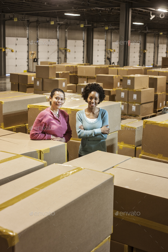 Team portrait of two African American female warehouse workers surrounded by products stored in - Stock Photo - Images