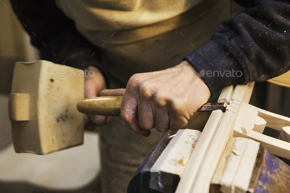 Close up of a man standing at a work bench in a carpentry workshop, working on a wooden chair with a - Stock Photo - Images