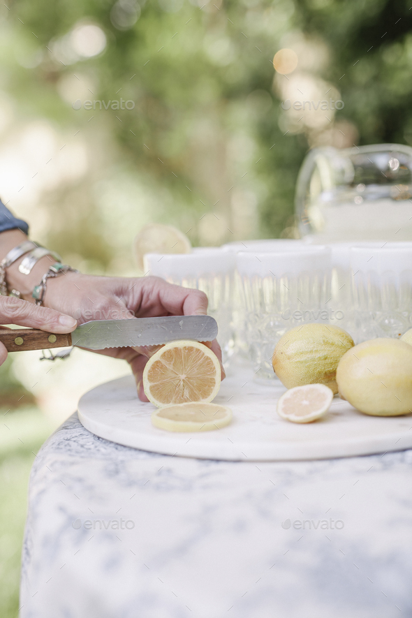 Close up of a woman standing at a table in a garden, slicing lemons for a drink. - Stock Photo - Images