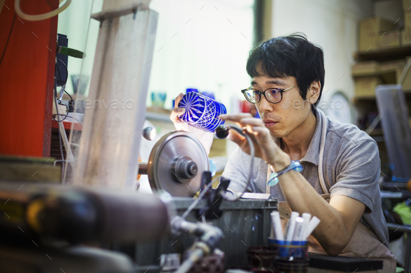 A craftsman at work in a glass maker's workshop polishing a vivid blue cut glass object. - Stock Photo - Images