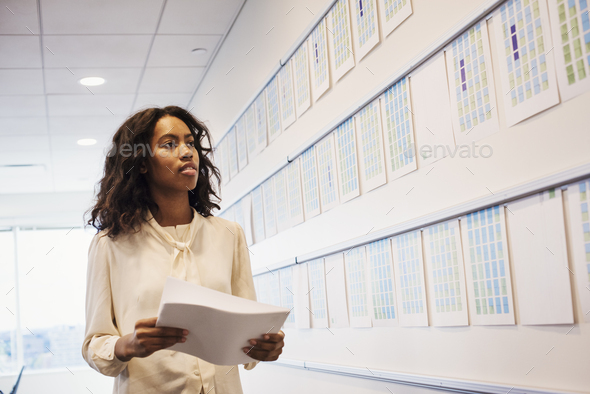 A woman standing in an office looking at a display holding pieces of paper. - Stock Photo - Images