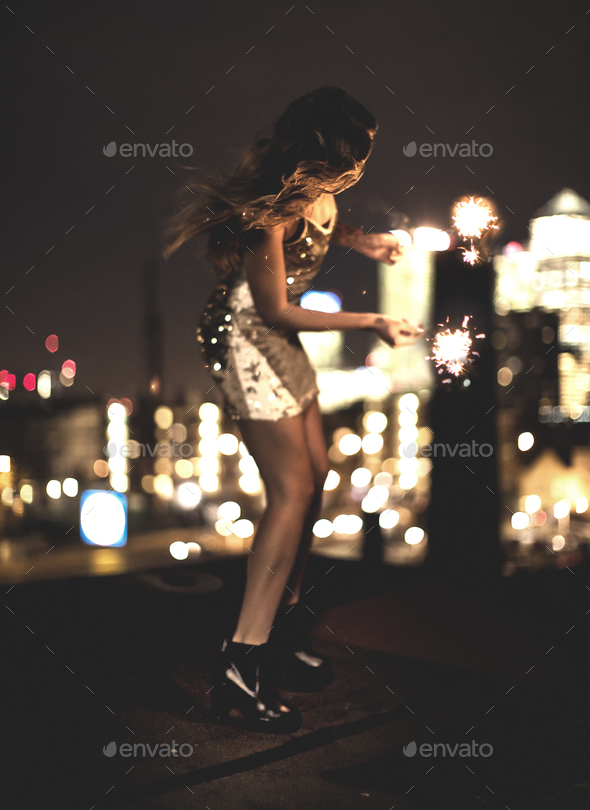 A young woman holding a sparkler and dancing on a building rooftop at night - Stock Photo - Images