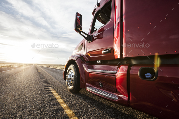 Close up side view looking forward of a commercial truck on a highway at sunset. - Stock Photo - Images