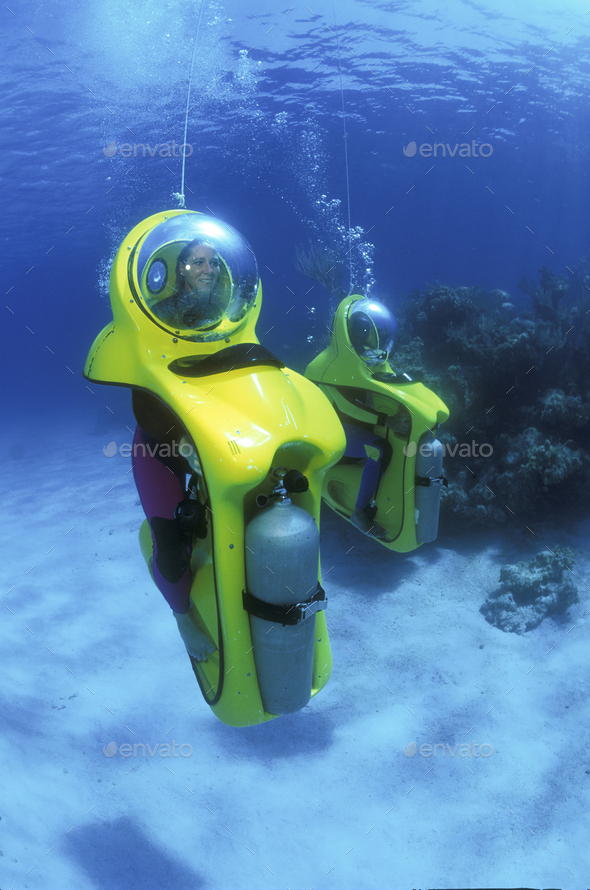 Two divers in Breathing Observation Submersible Scooters, underwater vehicles moving through the - Stock Photo - Images