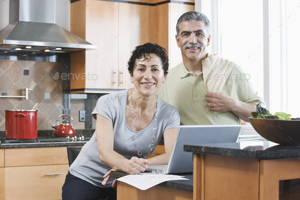 Caucasian man and woman in a kitchen using a laptop. - Stock Photo - Images