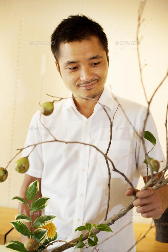 Japanese man standing in flower gallery, working on Ikebana arrangement. - Stock Photo - Images