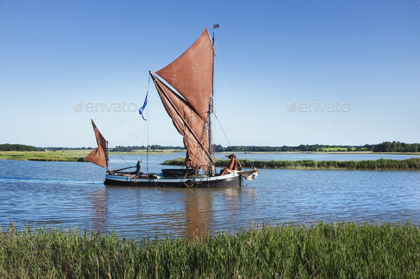 Traditional sailing boat with red sails and a gaff rig, a sailing smack on the water on a reed bed - Stock Photo - Images