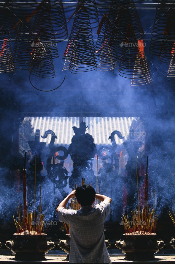 Rear view of person standing in front of shrine with incense burners. - Stock Photo - Images