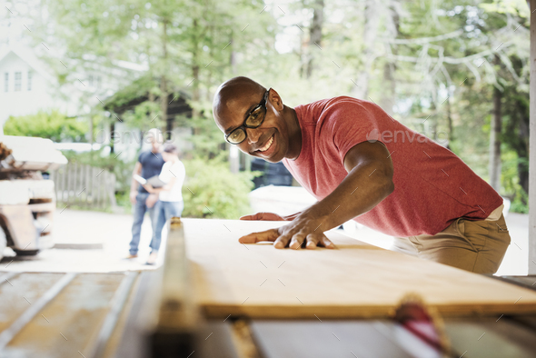 Man wearing glasses working in a lumber yard. - Stock Photo - Images