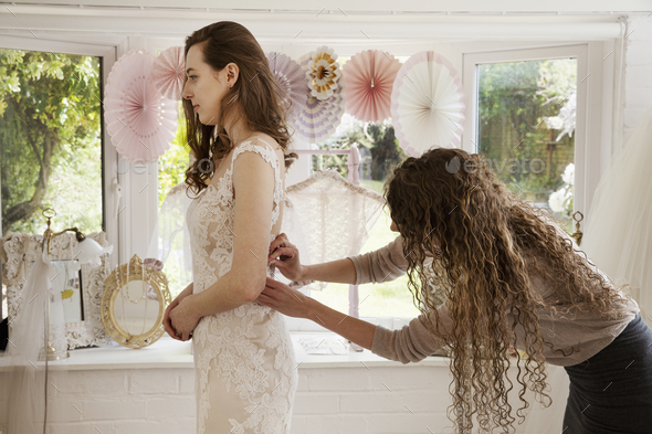A dressmaker taking in a wedding dress, pinning and fitting it to the client, a young woman. A bride - Stock Photo - Images