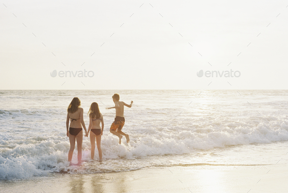 Three children playing on a sandy beach by the ocean. - Stock Photo - Images