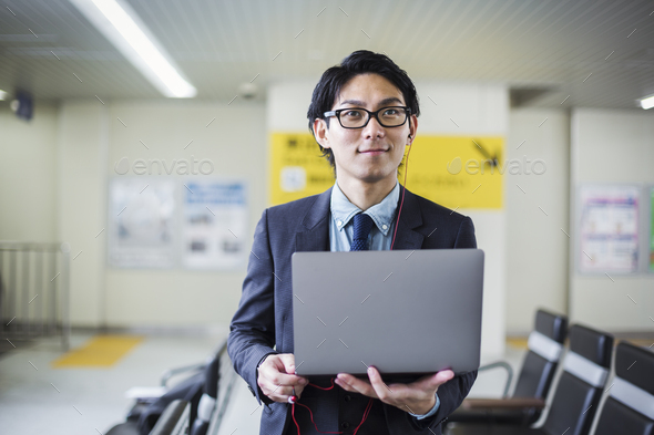 Businessman wearing suit and glasses standing at train station, holding laptop. - Stock Photo - Images