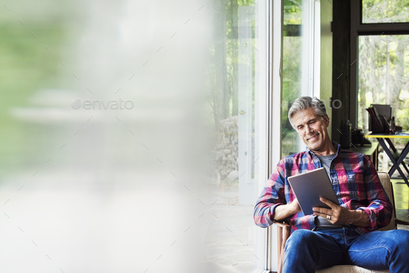 A man seated by a window reading using a digital tablet.  Blurred foreground. - Stock Photo - Images