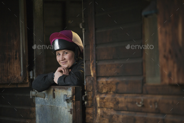Woman wearing a riding helmet standing in a box stall in a stable. - Stock Photo - Images