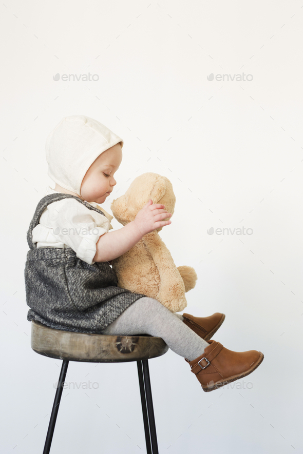 A young child, a girl sitting on a tall stool holding a teddy bear. - Stock Photo - Images