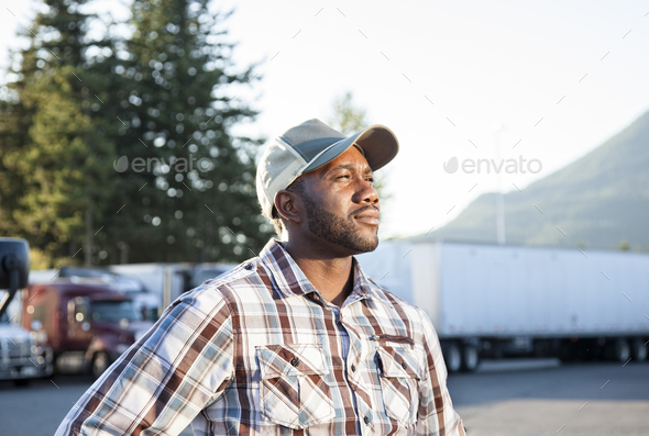 Black man truck driver near his truck parked in a parking lot at a truck stop - Stock Photo - Images