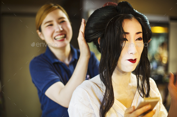 A geisha or maiko with a hair and make up artist creating the traditional hair style and make up. - Stock Photo - Images