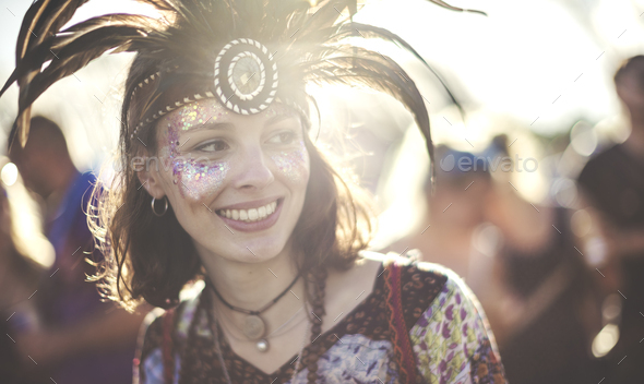 Young woman at a summer music festival wearing feather headdress and face painted, smiling. - Stock Photo - Images